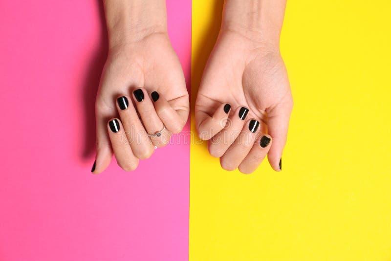 Vrouw die manicure met zwart nagellak op kleurenachtergrond tonen royalty-vrije stock fotografie