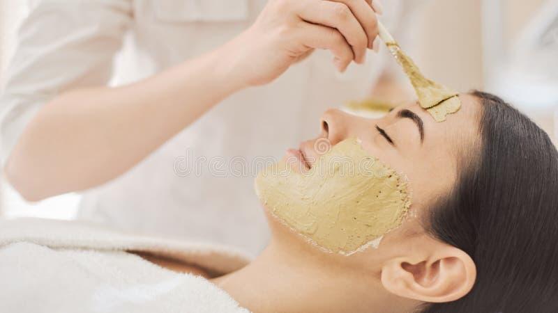 Vrouw die masker in kuuroord krijgen royalty-vrije stock afbeeldingen