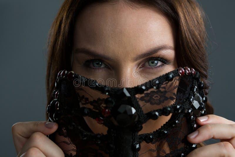 Vrouw die maskerademasker dragen tegen zwarte achtergrond royalty-vrije stock foto