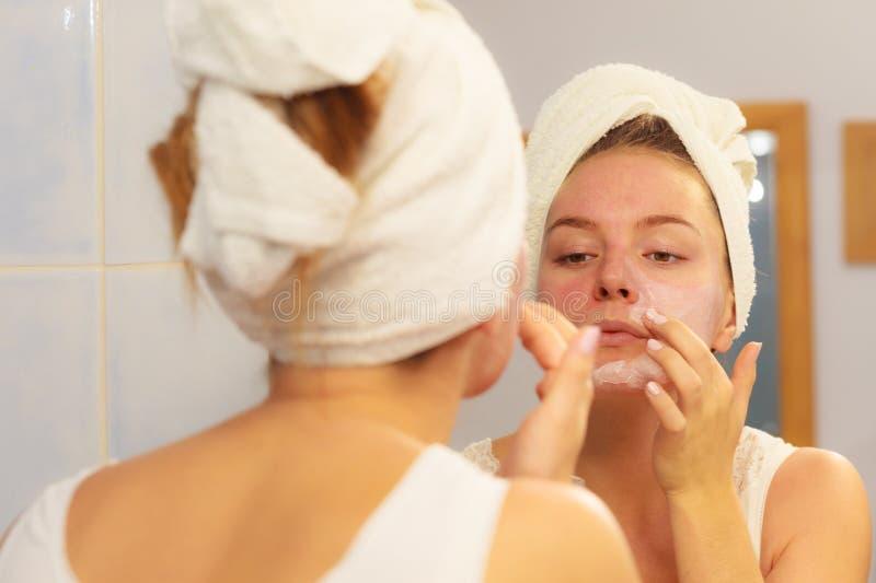 Vrouw die maskerroom op gezicht in badkamers toepassen royalty-vrije stock afbeelding