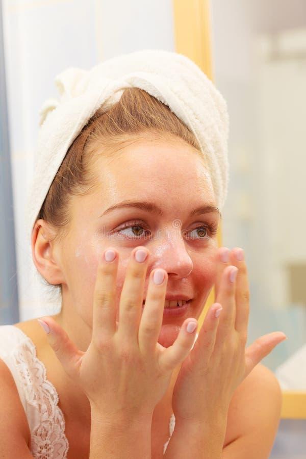 Vrouw die maskerroom op gezicht in badkamers toepassen royalty-vrije stock foto