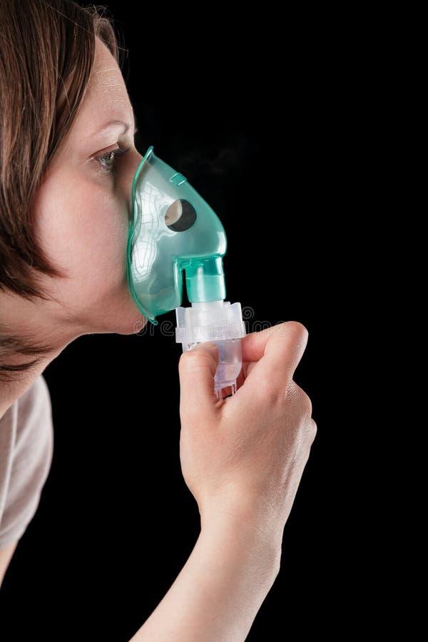 Vrouw die medische die inhalatie doen op zwarte wordt geïsoleerd stock afbeelding