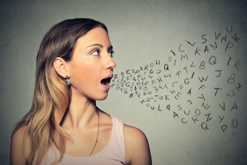Vrouw die met alfabetbrieven spreken die uit haar mond komen stock foto's