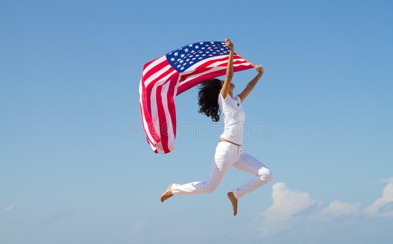 Vrouw die met Amerikaanse vlag springt stock fotografie