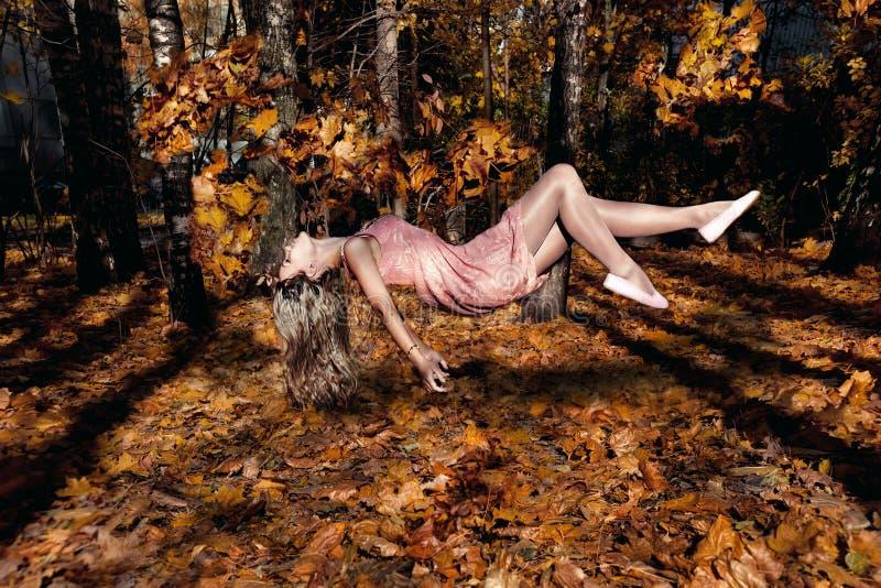 Vrouw die met auumnbladeren vliegen. Levitatie stock foto's