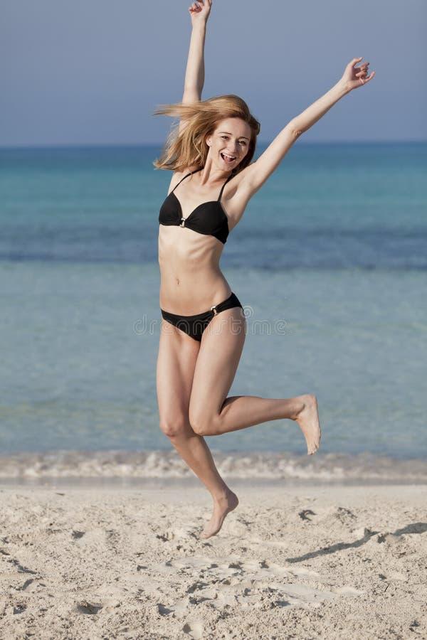 Vrouw die met bikini gelukkig op het strandportret springen royalty-vrije stock fotografie