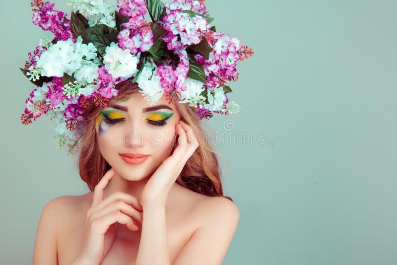 Vrouw die met bloemen op hoofd gele en groene oogschaduw gesloten ogen glimlachen royalty-vrije stock fotografie