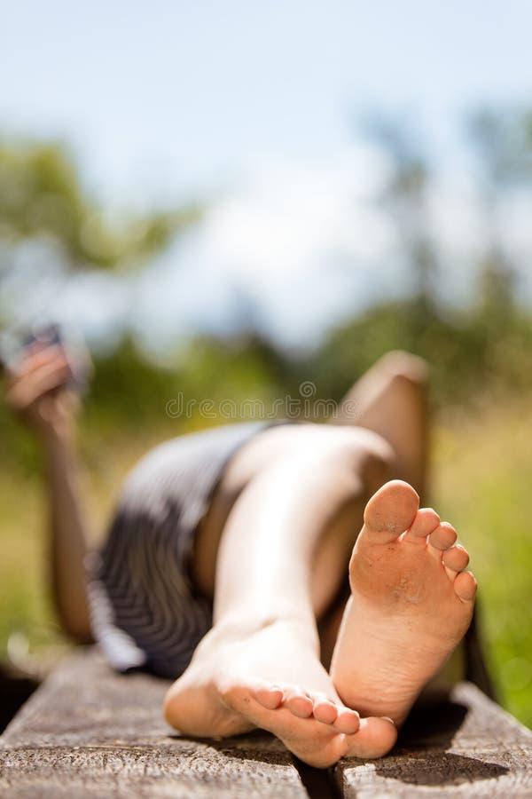 Vrouw die met blootvoetse voeten op een houten zetel, het ontspannen liggen stock foto's