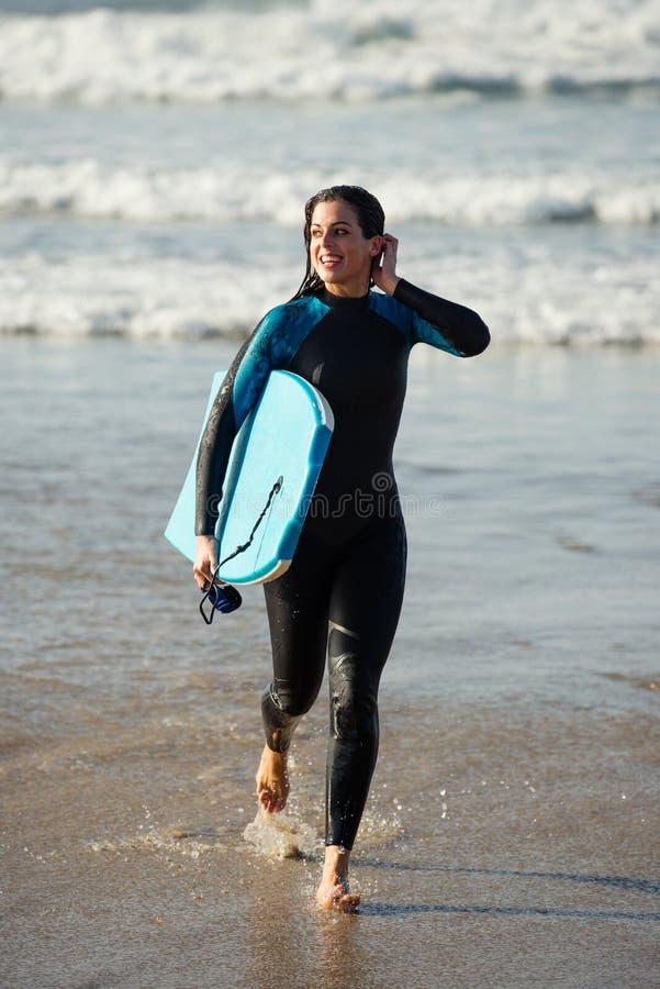 Vrouw die met bodyboard na het surfen weggaan stock fotografie