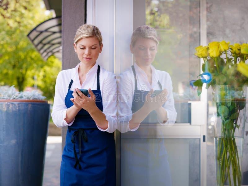 Vrouw die met cellphone als bloemist in winkel werkt royalty-vrije stock afbeelding