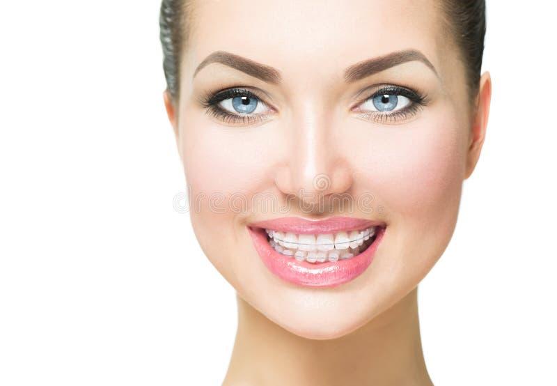 Vrouw die met ceramische steunen op tanden glimlachen stock foto