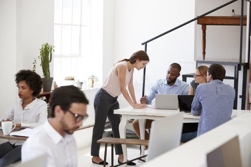 Vrouw die met collega's bij een bureau in open planbureau werken stock fotografie