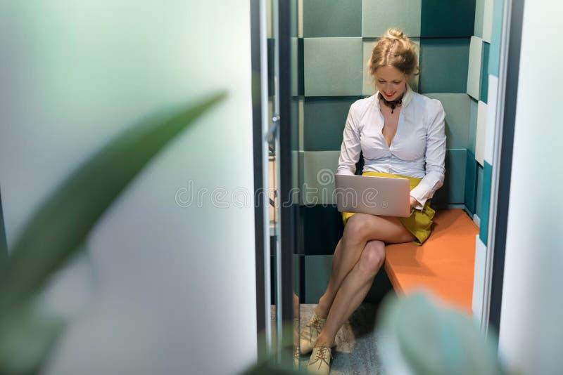 Vrouw die met computer in stille cabine werken stock afbeeldingen