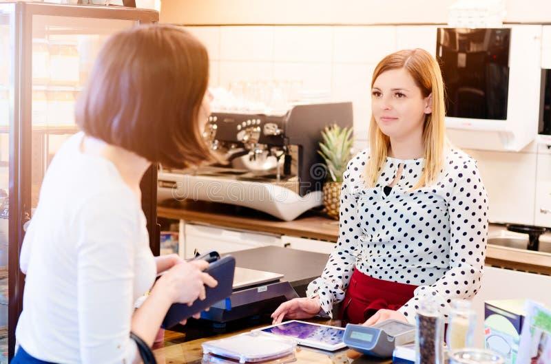 Vrouw die met contant geld voor koffie betalen stock afbeeldingen