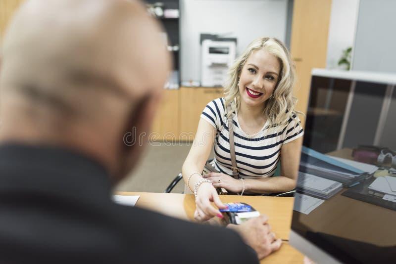 Vrouw die met creditcard in bedrijfbureau betalen royalty-vrije stock fotografie