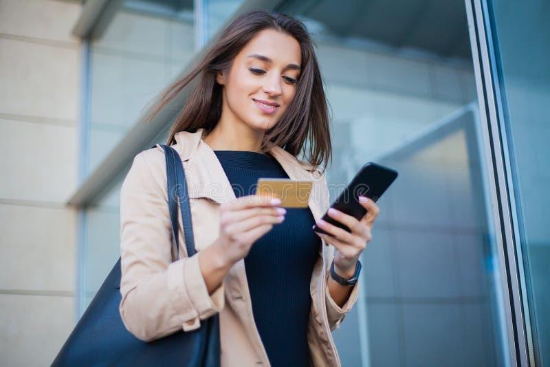 Vrouw die met creditcard winkelen Mooie jonge dame met gouden kaart die telefoon met behulp van royalty-vrije stock foto's