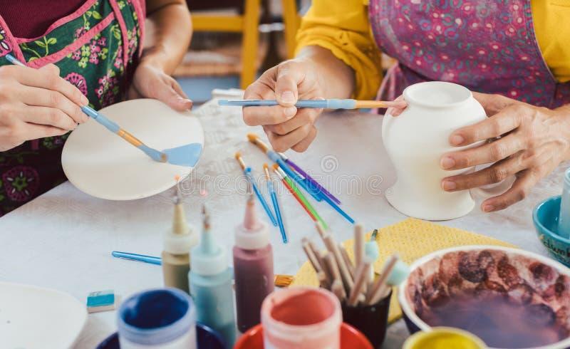 Vrouw die met de hand gemaakte schotels kleuren die borstel en kleur gebruiken royalty-vrije stock fotografie
