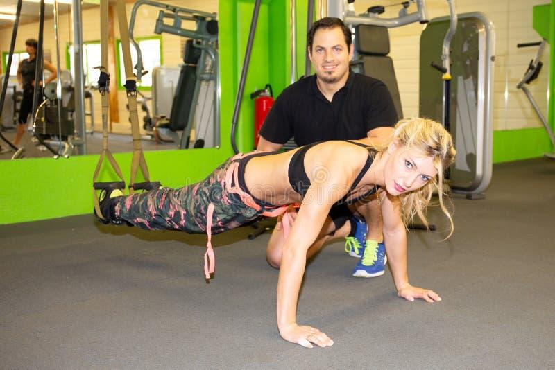 Vrouw die met de man van de gymnastiekbus opschortingsriemen uitoefenen in geschiktheidsclub opleiding royalty-vrije stock fotografie