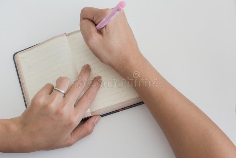 Vrouw die met diamantring in een agenda schrijven stock fotografie