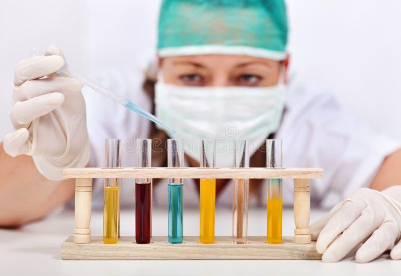 Vrouw die met diverse vloeistoffen in test-buizen experimenteren royalty-vrije stock foto's