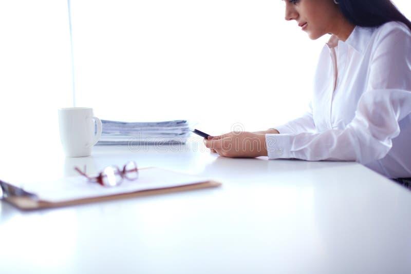 Download Vrouw Die Met Documenten Op Het Bureau Zitten Stock Afbeelding - Afbeelding bestaande uit zeker, elegant: 107703009