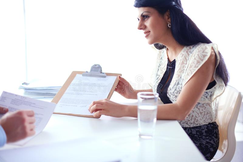 Download Vrouw Die Met Documenten Op Het Bureau Zitten Stock Foto - Afbeelding bestaande uit meisje, toekomst: 107703066