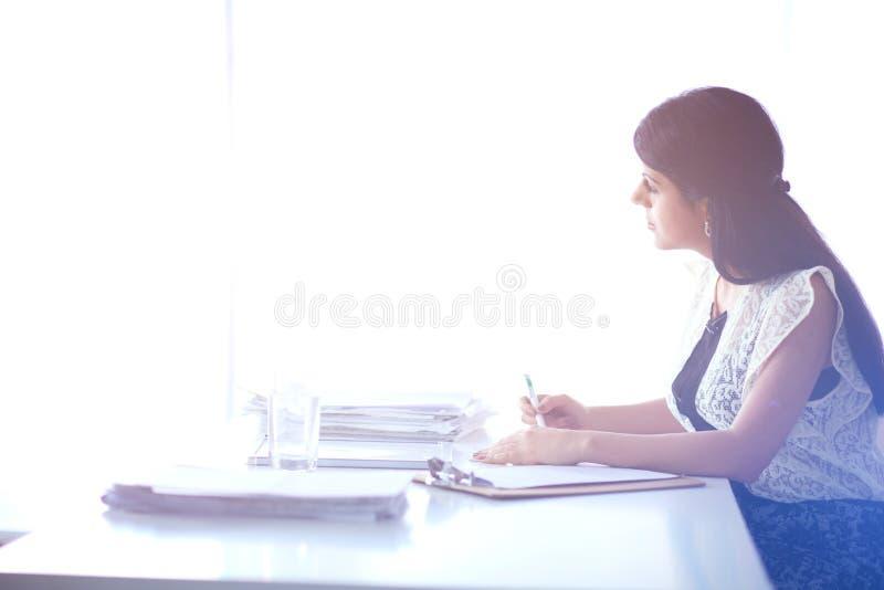 Download Vrouw Die Met Documenten Op Het Bureau Zitten Stock Afbeelding - Afbeelding bestaande uit financieel, levensstijl: 107704131