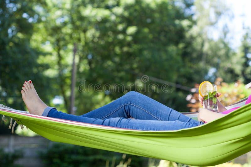 Vrouw die met drank op hangmat rusten stock foto's