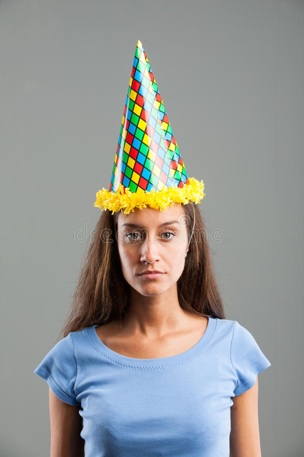Vrouw die met droefheid kijken terwijl het dragen van partijhoed stock afbeeldingen