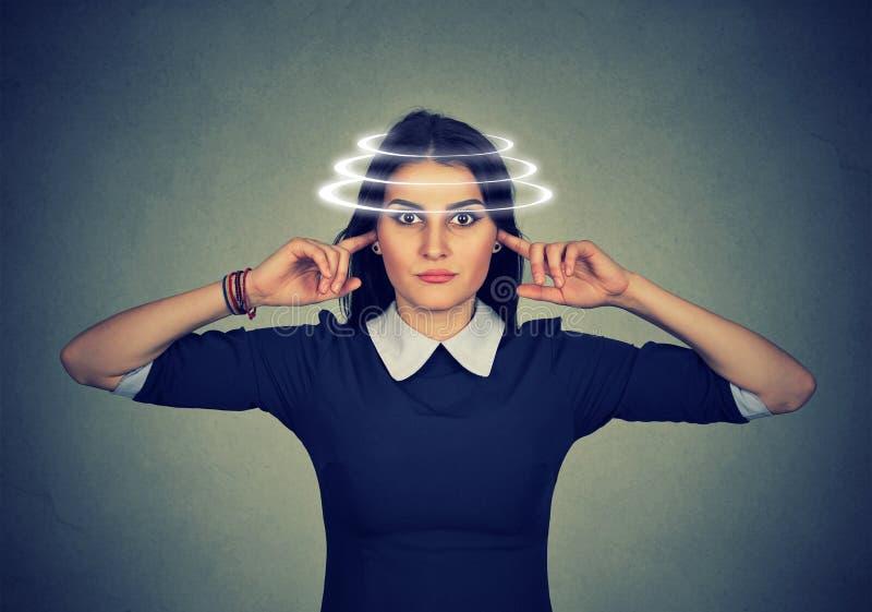 Vrouw die met duizeligheid haar oren van lawaai sluiten stock fotografie