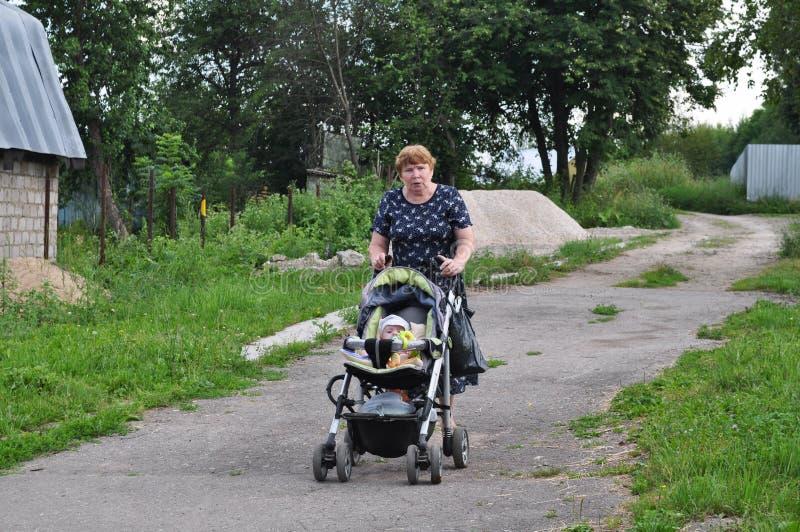 Vrouw die met een baby in een wandelwagen lopen stock foto