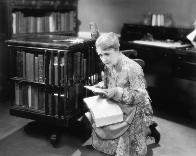 Vrouw die met een boek in haar bibliotheek knielen die een brief vinden (Alle afgeschilderde personen leven niet langer en geen l royalty-vrije stock afbeeldingen