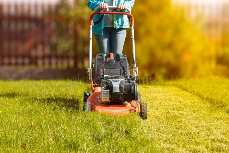 Vrouw die met een grasmaaier werken royalty-vrije stock fotografie