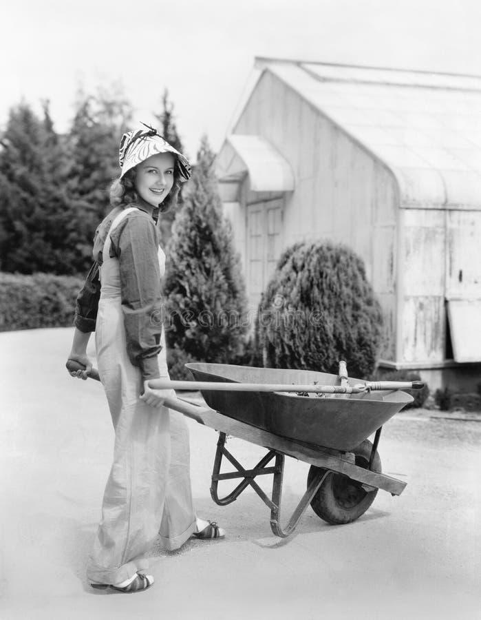 Vrouw die met een wielvat lopen (Alle afgeschilderde personen leven niet langer en geen landgoed bestaat Leveranciersgaranties di stock foto's