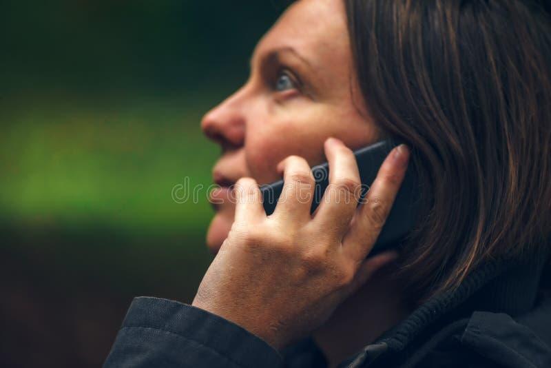 Vrouw die met ernstige gezichtsuitdrukking op telefoon in park spreken royalty-vrije stock foto