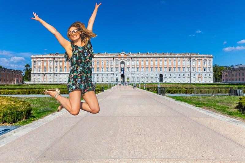 Vrouw die met geluk met omhoog wapens springen Koninklijk paleis van Caserta in Italië Reis in Italië royalty-vrije stock foto