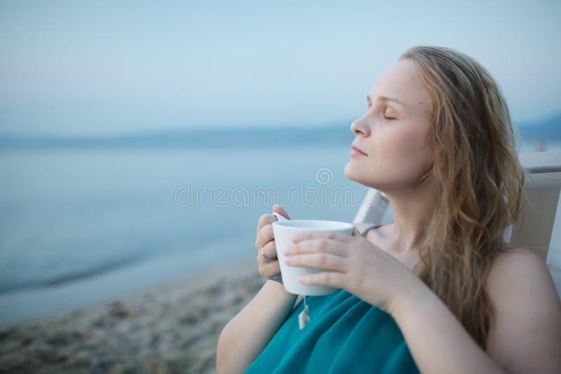 Vrouw die met gesloten ogen van een kop thee genieten bij royalty-vrije stock fotografie