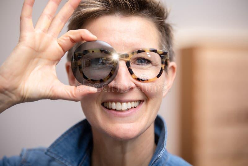 Vrouw die met glazen door gekleurd glas kijkt royalty-vrije stock foto