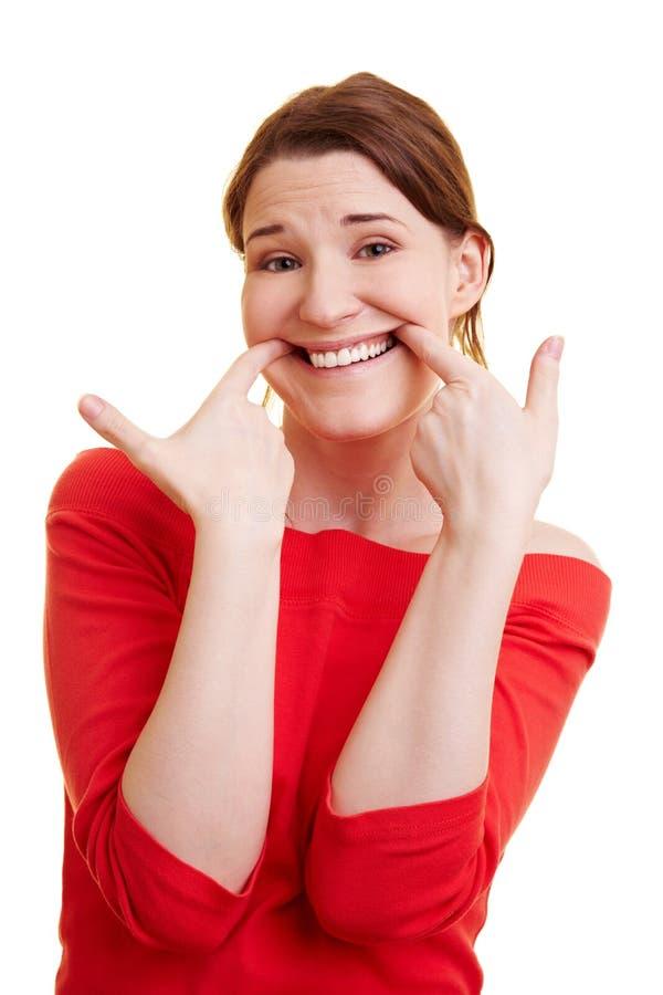 Vrouw die met haar vingers grimassen trekt stock afbeeldingen