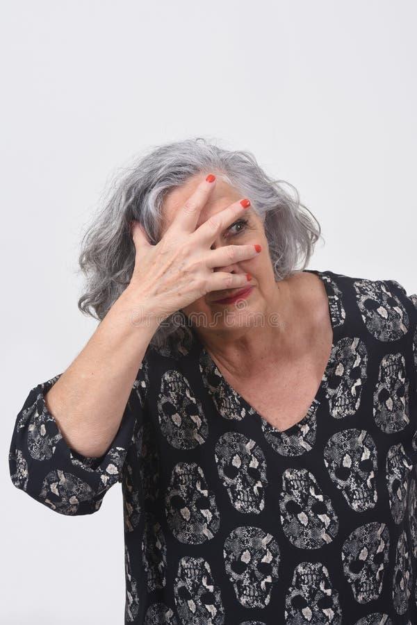 Vrouw die met hand op gezicht op witte achtergrond gluren stock foto