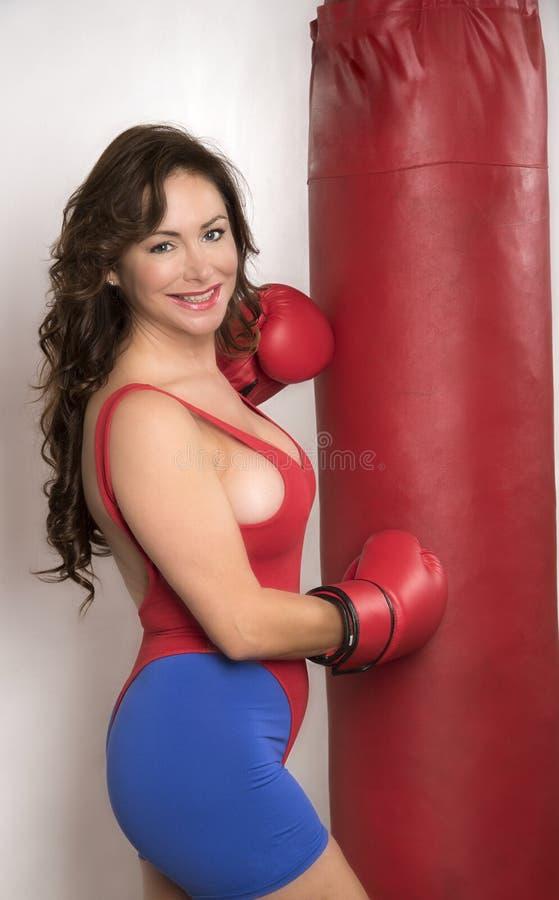 Vrouw die met handschoenen en een punchbag uitwerken stock foto