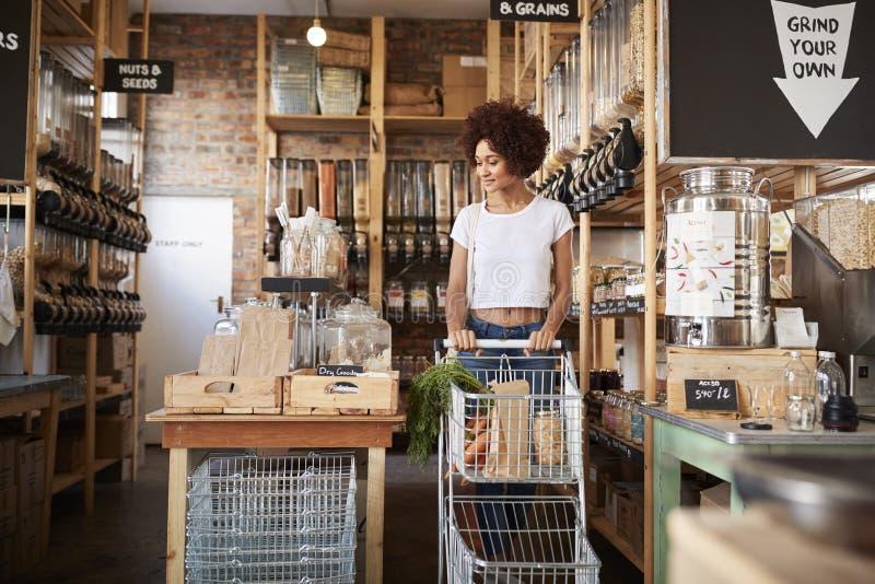 Vrouw die met het Winkelen Karretje Vers Fruit en Groenten in Plastic Vrije Kruidenierswinkelopslag kopen stock foto's