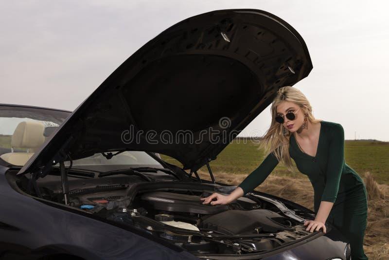Vrouw die met hielen haar gebroken auto herstellen stock afbeelding