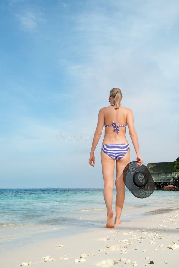Vrouw die met hoed langs tropisch strand lopen royalty-vrije stock fotografie