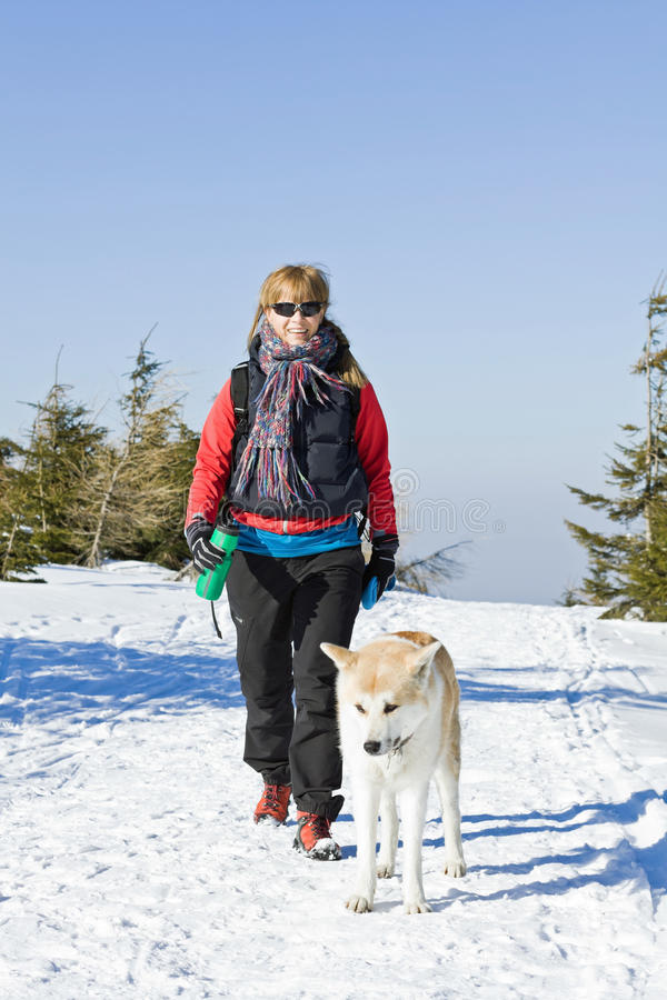 Vrouw die met hond in de winter wandelt royalty-vrije stock afbeeldingen