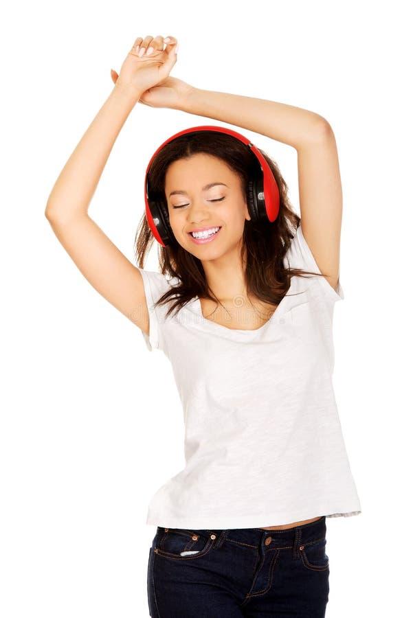 Vrouw die met hoofdtelefoons aan muziek luistert stock foto