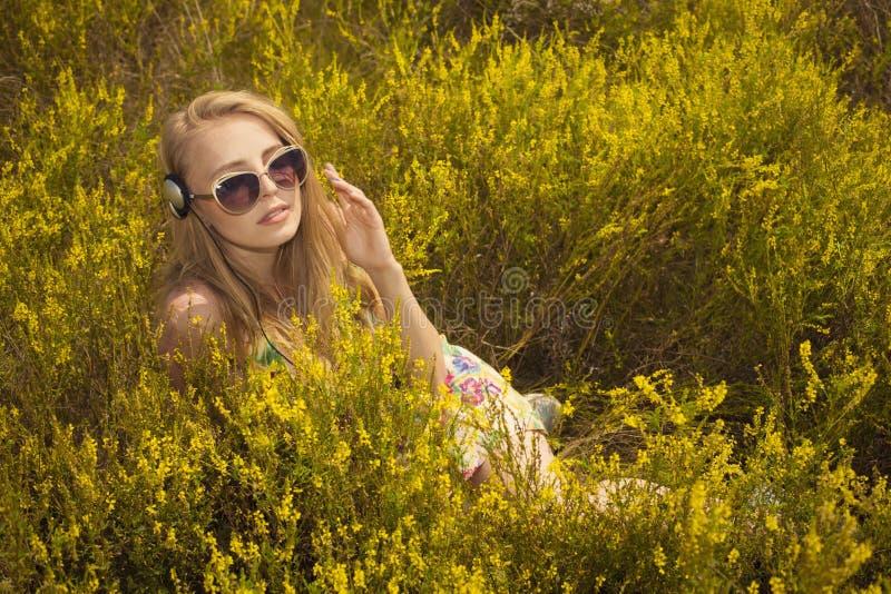 vrouw die met hoofdtelefoons in openlucht gebied van muziek genieten royalty-vrije stock afbeelding