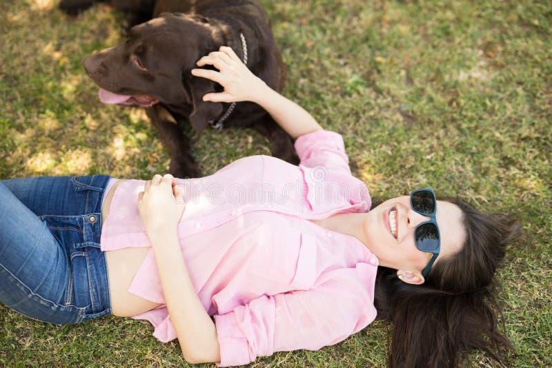 Vrouw die met huisdierenhond genieten van royalty-vrije stock afbeelding