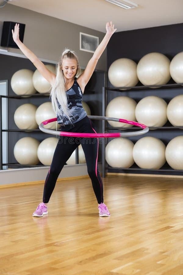 Vrouw die met Hula-Hoepel in Gymnastiek uitoefenen stock fotografie