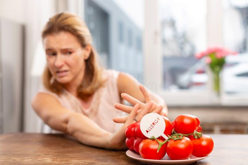 Vrouw die met hypergevoeligheid aan allergenen geen tomaten eten stock afbeelding